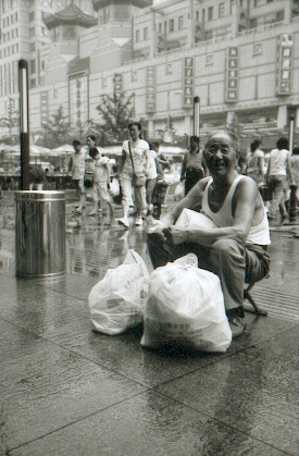 pekin-88-rue-principale-ramasseur-de-bouteille-assis